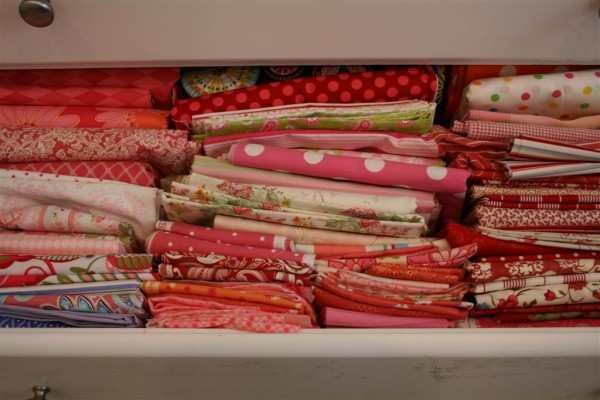 drawer filled with pink and red fabrics
