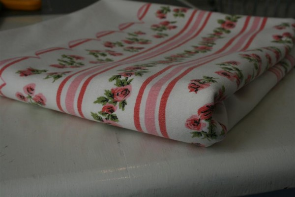 folded pink and white vintage tablecloth
