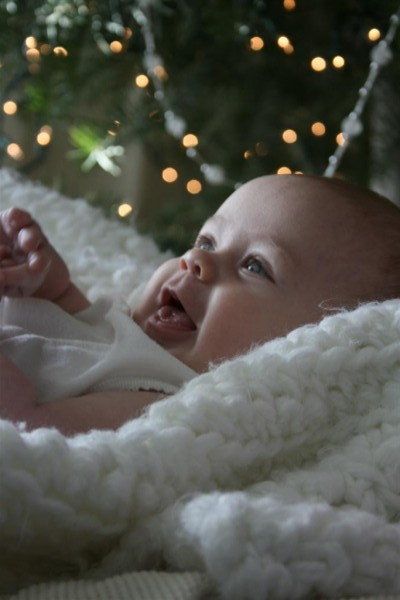 baby smiling in front of Christmas tree