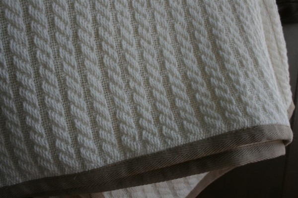 cable knit blanket with contrasting twill trim