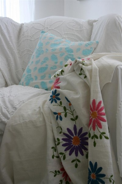 vintage turquoise pillow and embroidered coverlet