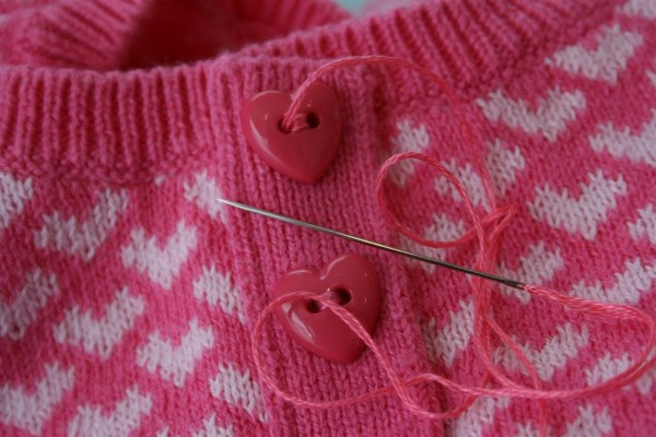 pink sweater with heart buttons and needle